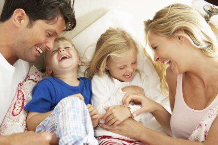 tickling: Family Relaxing Together In Bed