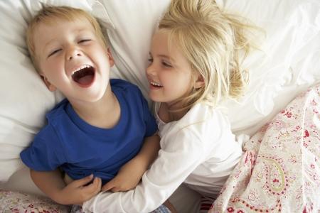 pijama: Hermano y hermana relajante juntos en la cama