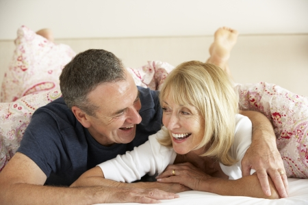couples hug: Senior Couple Relaxing Together In Bed