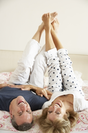 sexy woman on bed: Senior Couple Lying Upside Down Together In Bed Stock Photo