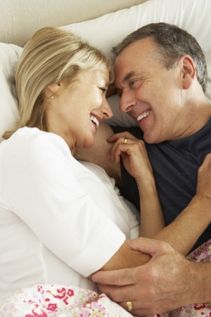 sexy woman on bed: Senior Couple Relaxing Together In Bed