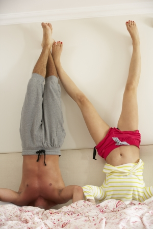 headstand: Couple Standing On Head In Bed Stock Photo