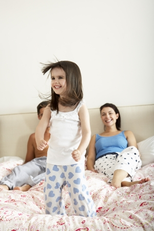 Family Bouncing On Bed Together photo