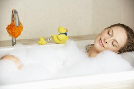 pato de hule: La mujer se relaja en baño de burbujas Lleno