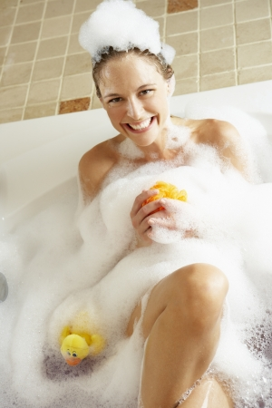 Woman Relaxing In Bubble Filled Bath photo