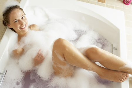 lying in bathtub: Woman Relaxing In Bubble Filled Bath Stock Photo