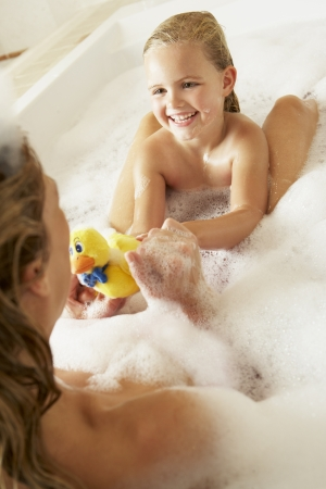 bath time: Mother And Daughter Relaxing In Bubble Filled Bath Stock Photo
