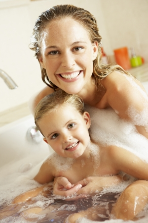 child bath: Mother And Daughter Relaxing In Bubble Filled Bath Stock Photo