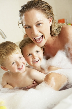 woman in bath: Mother With Children Relaxing In Bubble Filled Bath Stock Photo