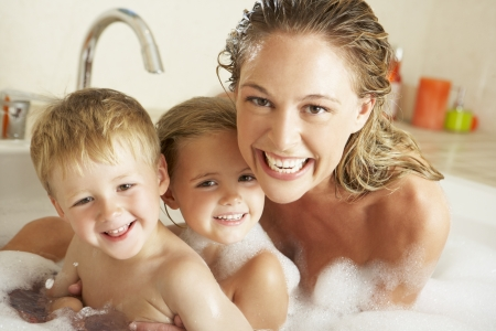 Mother With Children Relaxing In Bubble Filled Bath photo