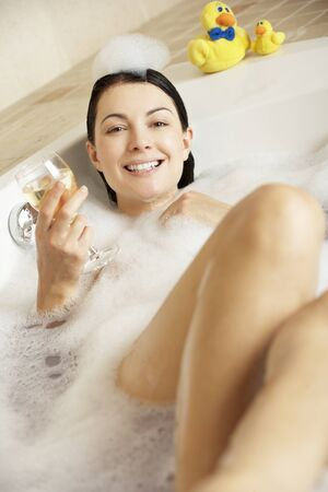 Woman Relaxing With Glass Of Wine In Bubble Filled Bath Stock Photo - 18719078