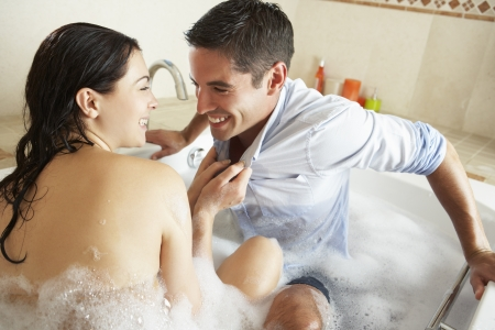 Woman Pulling Clothed Man Into Bubble Filled Bath photo
