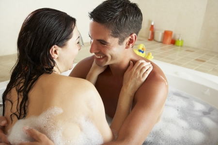 Couple Relaxing In Bubble Filled Bath photo