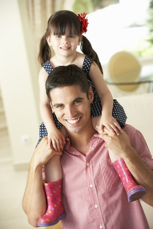 Father Giving Daughter Ride On Shoulders Indoors photo