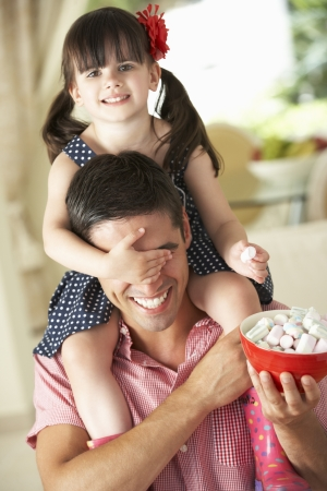 Father Giving Daughter Ride On Shoulders Indoors Whilst Eating Marshmallows photo