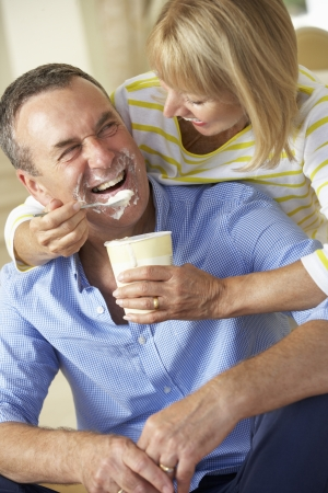Senior Woman Feeding Husband Ice Cream photo