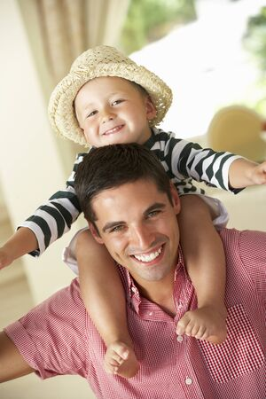 Father Giving Son Ride On Shoulders Indoors photo