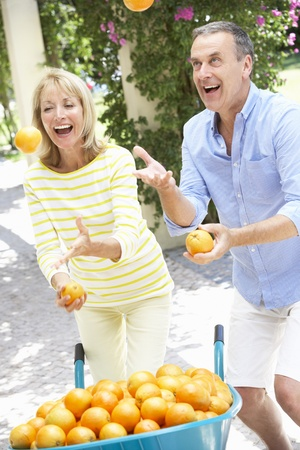 Senior Couple Juggling Oranges In Front Of Wheelbarrow photo