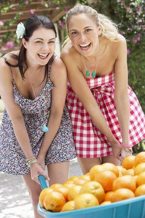 thirties portrait: Two Women Pushing Wheelbarrow Filled With Oranges Stock Photo