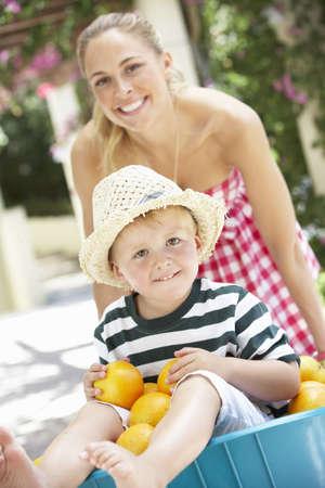 mujer hijos: Hijo de la madre empuja en carretilla lleno de naranjas