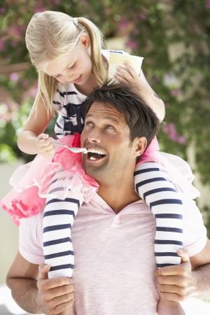 hombros: Padre que da paseo hija a hombros mientras que siendo Cream Ice Fed