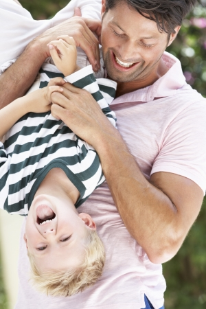 dad and child: Father Holding Son Upside Down Outdoors