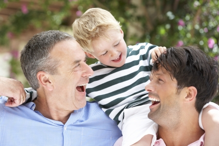 grandfather and grandson: Grandfather And Father Giving Grandson Ride On Shoulders Stock Photo