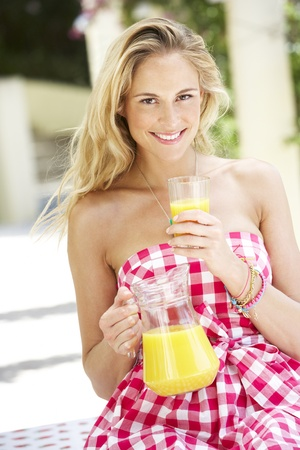 Woman Enjoying Glass Of Orange Juice photo