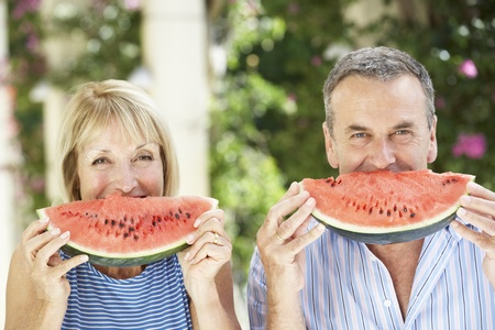 Senior Couple Enjoying Slices Of Water Melon photo