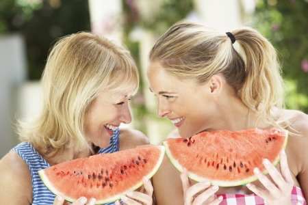 grown ups: Mother And Adult Daughter Enjoying Slices Of Water Melon