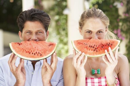 Couple Enjoying Slices Of Water Melon photo