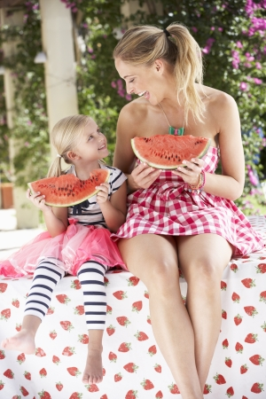 frutas divertidas: Madre e hija disfrutando de rodajas de melón de agua Foto de archivo