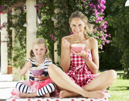 two year old: Mother And Daughter Enjoying Breakfast Cereal Outdoors Together