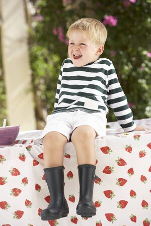 Young Boy Wearing Wellington Boots Sitting On Table Stock Photo