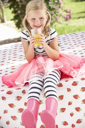 5 year old girl: Young Girl Wearing Pink Wellington Boots Drinking Orange Juice