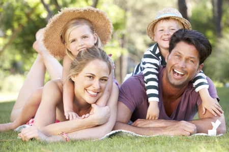 four person: Family Relaxing In Park Together