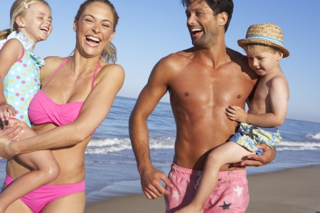guy on beach: Family Having Fun On Beach Stock Photo