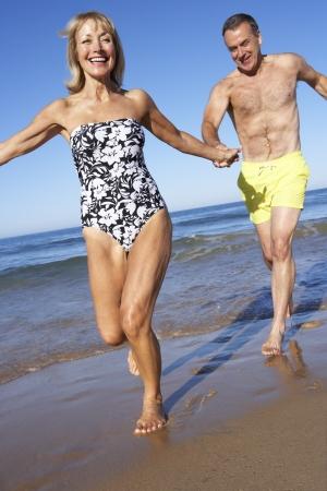 fit couple: Senior Couple Enjoying Beach Holiday Stock Photo