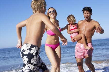 5 10 year old girl: Family Having Fun On Beach Stock Photo