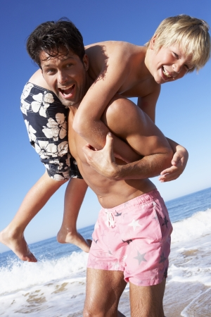 10 year old: Father And Son Having Fun On Beach Stock Photo