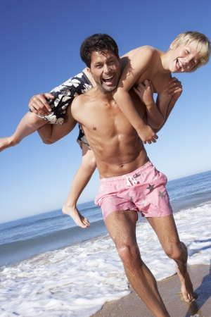 swimming shorts: Father And Son Having Fun On Beach Stock Photo