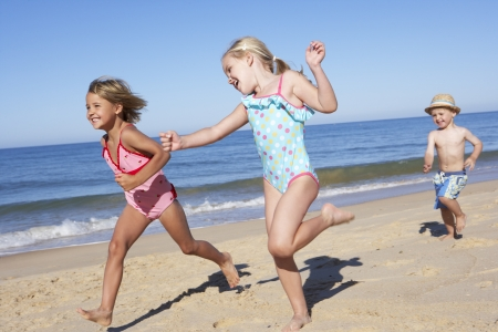 enfant maillot: Trois enfants courant le long de la plage Banque d'images