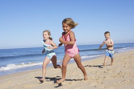 Drie kinderen die langs Strand
