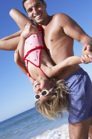 Father And Daughter Having Fun On Beach photo