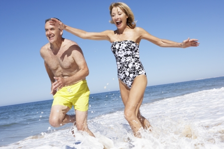 active holiday: Senior Couple Enjoying Beach Holiday Stock Photo