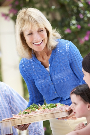 Senior Woman Serving At Multi Generation Family Meal Stock Photo - 18723253