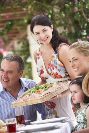 Woman Serving At Multi Generation Family Meal Stock Photo - 18722560