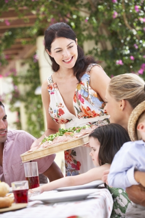entertaining: Woman Serving At Family Meal Stock Photo