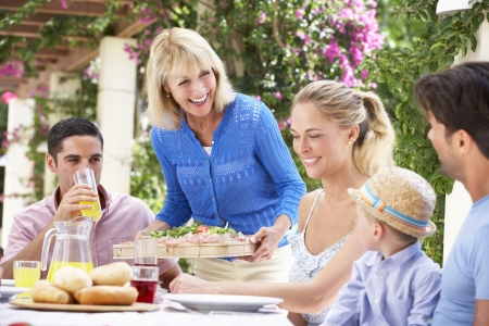 Senior Woman Serving At Multi Generation Family Meal Stock Photo - 18723161