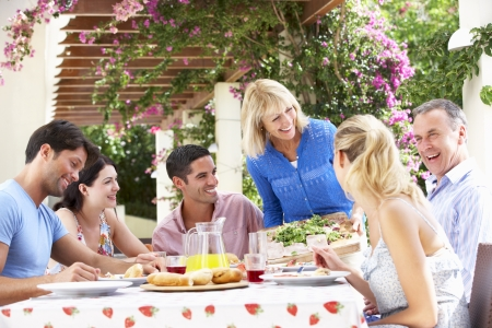 grown ups: Group Of Young And Senior Couples Enjoying Family Meal
